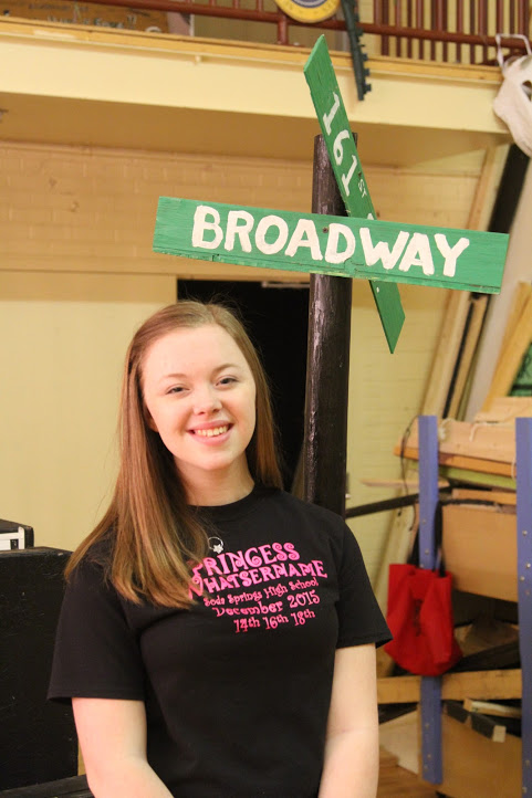 Senior Brynja Stalcup poses in front of a Broadway sign.