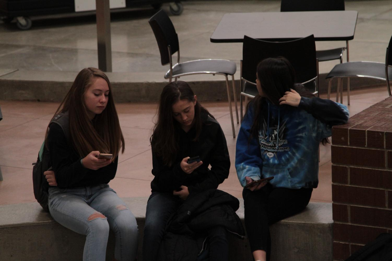 A group of students sit in the mall, each one with a cell phone in hand.