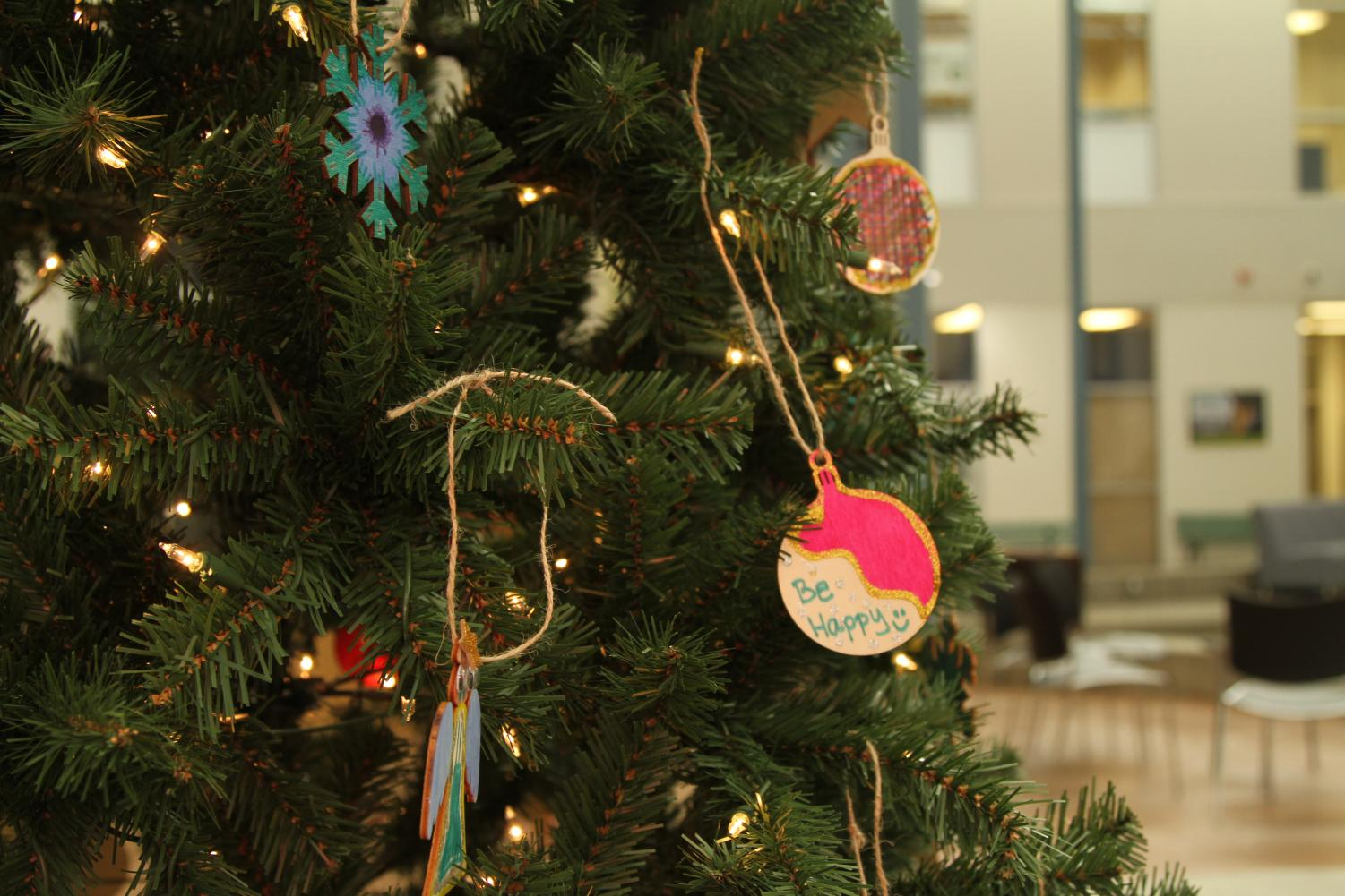 Several student-decorated ornaments hang from the Christmas tree in the school mall.