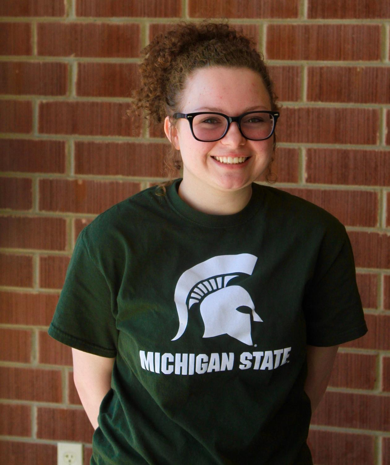 Senior Kathleen Farmer smiles poses in her Michigan State T-shirt. Taken by Emmie Baker.